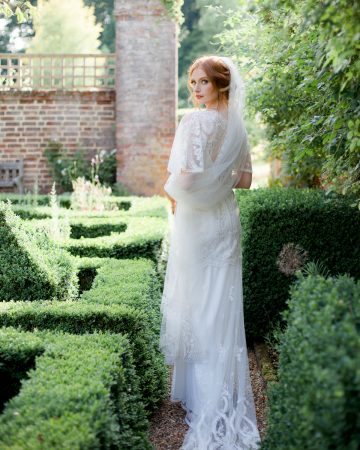 romantic wedding photography- a bride walking down a topiary path at Bignor Park