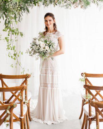 romantic wedding photography- a bride under a floral arbour
