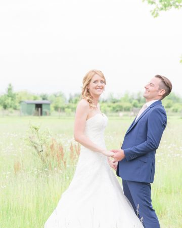 romantic wedding photography- a couple stand in a wildflower meadow
