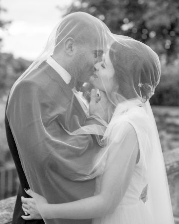 romantic wedding photography- a bride and groom kiss under a veil