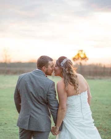 romantic wedding photography- a bride and groom kiss at sunset