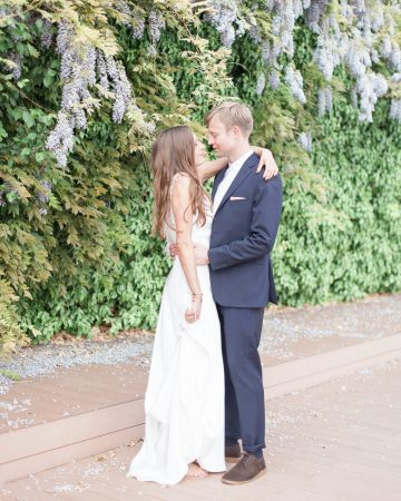 romantic wedding photography- a bride and groom by a wisteria hedge