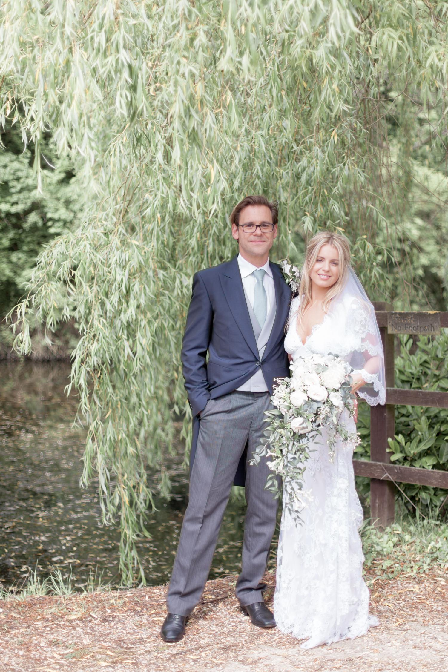 Emily & Jonathan's Cambridgeshire wedding - couple standing next to weeping willow